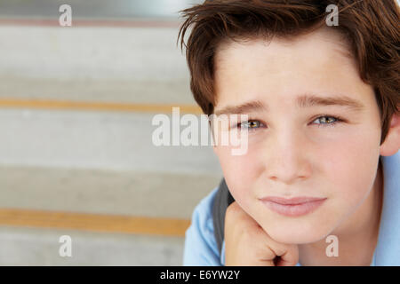 Unhappy Pre teen boy at school - Stock Photo
