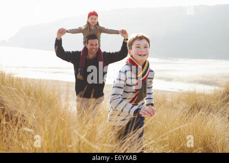 Father And Children Walking Through Dunes On Winter Beach - Stock Photo