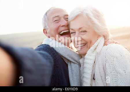 Senior Couple Standing On Beach Taking Selfie - Stock Photo
