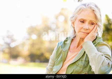 Depressed Senior Woman Sitting Outside - Stock Photo