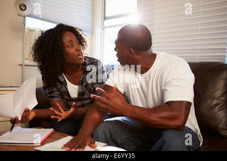 Worried Couple Sitting On Sofa Arguing About Bills - Stock Photo