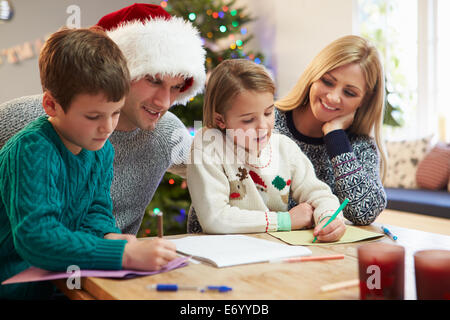 Family Writing Christmas Cards Together - Stock Photo