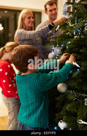 Family Decorating Christmas Tree At Home Together - Stock Photo