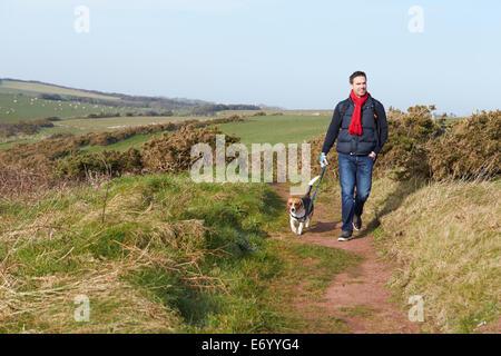 Man With Dog Walking Along Coastal Path - Stock Photo