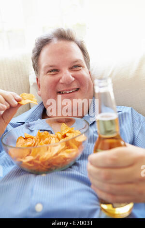 Overweight Man At Home Eating Chips And Drinking Beer
