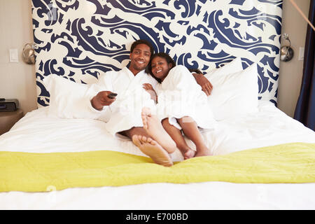 Couple Relaxing In Hotel Room Watching Television - Stock Photo