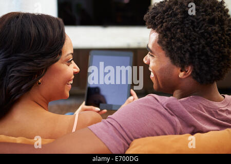 Rear View Of Couple Sitting On Sofa Using Digital Tablet - Stock Photo