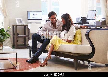Couple Sitting On Sofa In Hotel Lobby - Stock Photo