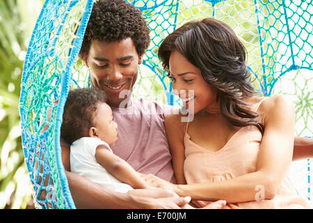Family With Baby Relaxing On Outdoor Garden Swing Seat - Stock Photo