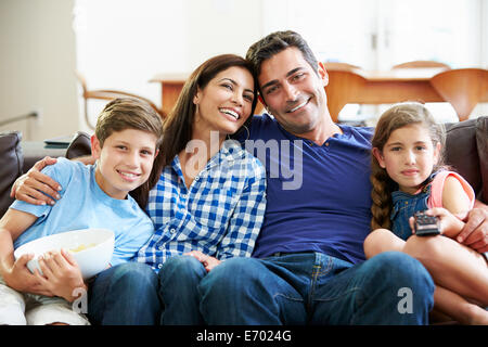 Family Sitting On Sofa Watching TV Together - Stock Photo