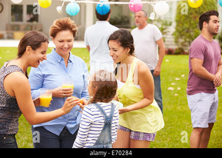 Multi Generation Family Enjoying Party In Garden Together - Stock Photo