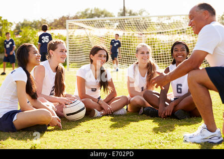 Coach Giving Team Talk To Female High School Soccer Team - Stock Photo