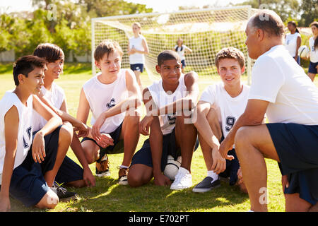 Coach Giving Team Talk To Male High School Soccer Team - Stock Photo