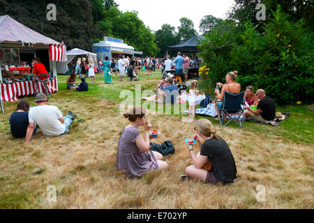 People sitting in the gardens at Strawberry Hill House eating strawberries at summer fair in Twickenham, London - Stock Photo