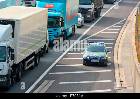 Essex Police BMW car using the hard shoulder to reach accident location at front of gridlocked motorway traffic - Stock Photo