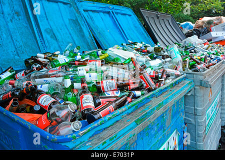 Rubbish bins overflowing with glass bottles in roadside recycling facility - Stock Photo