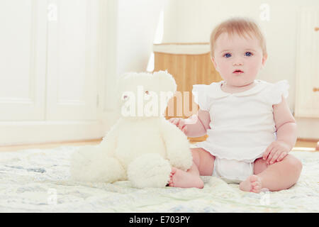 Portrait baby girl and teddy bear sitting on floor - Stock Photo