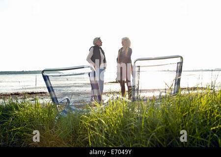 Mother and daughter chatting on beach - Stock Photo
