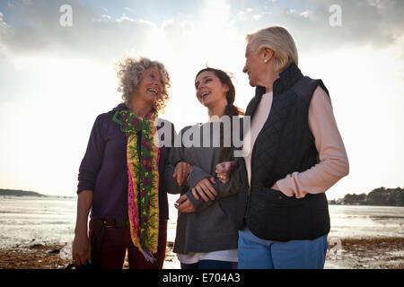 Female family members chatting on beach - Stock Photo