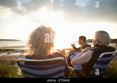 Family members relaxing by beach - Stock Photo