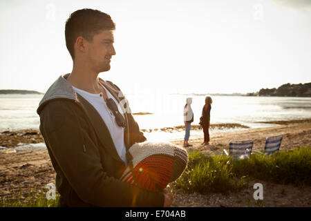 Young man holding blanket on Bournemouth beach, Dorset, UK - Stock Photo