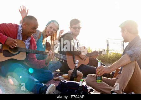 Four adult friends partying on Bournemouth beach, Dorset, UK - Stock Photo