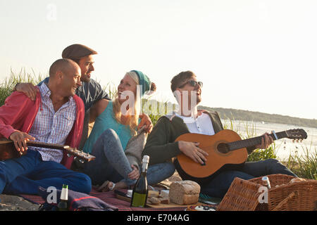 Four adult friends having a party on Bournemouth beach, Dorset, UK - Stock Photo