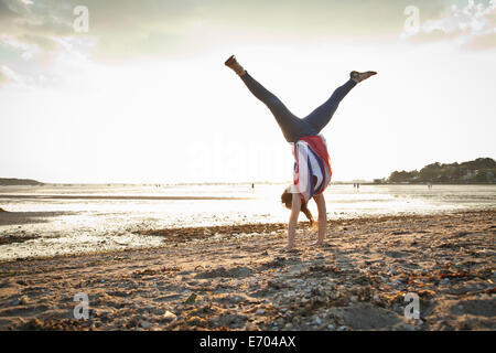 Young woman doing handstand on Bournemouth beach, Dorset, UK - Stock Photo