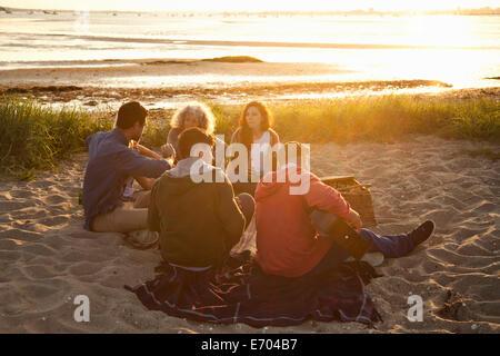 Five adult friends picnicing at sunset on Bournemouth beach, Dorset, UK - Stock Photo