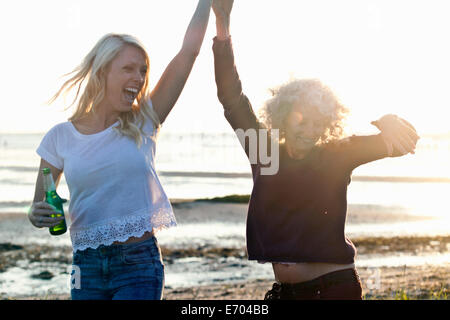 Mother and daughter dancing on Bournemouth beach, Dorset, UK - Stock Photo