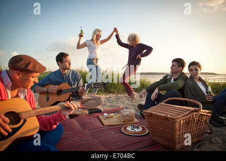 Six adult friends partying and dancing on Bournemouth beach, Dorset, UK - Stock Photo