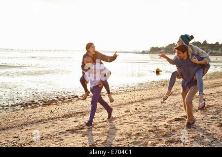 Men giving piggyback ride to women on beach - Stock Photo
