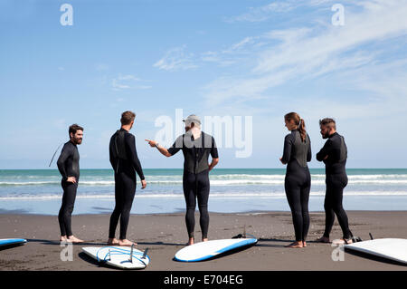 Group of male and female surfer friends chatting on beach - Stock Photo
