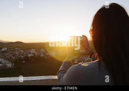 Young woman taking photo with smartphone, Mirador de Sachaca, Arequipa, Peru - Stock Photo