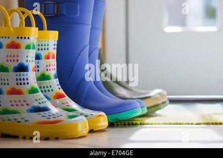 Close up side view of row of rubber boots at back door - Stock Photo