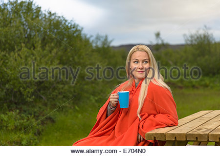 Mid adult woman sitting on bench, drinking coffee - Stock Photo