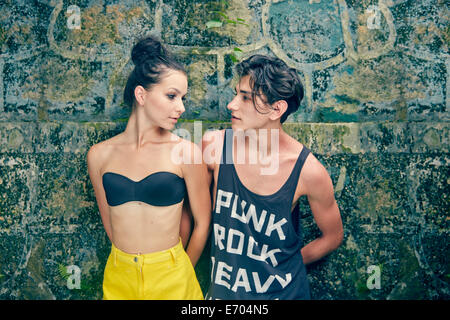Young couple standing against wall, looking at each other - Stock Photo