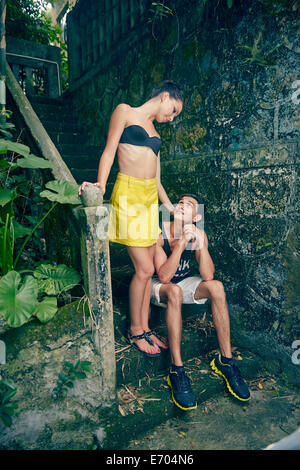Young couple on steps, looking at each other - Stock Photo