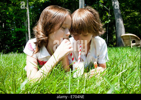 Brother and sister in woods sharing a milkshake - Stock Photo
