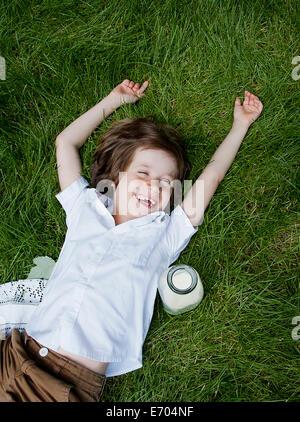 Boy lying on grass laughing - Stock Photo