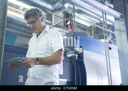 Engineer using digital tablet in power station - Stock Photo
