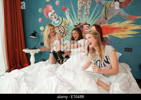 Four young women friends uncorking champagne on hotel bed - Stock Photo