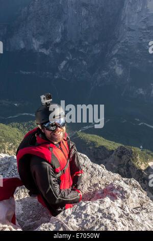 Portrait of BASE jumper on mountain edge, Alleghe, Dolomites, Italy - Stock Photo