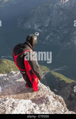 BASE jumper on mountain edge, Alleghe, Dolomites, Italy - Stock Photo