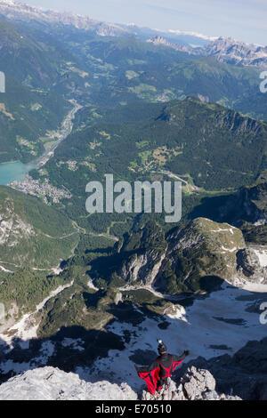 Male BASE jumper on mountain edge, Alleghe, Dolomites, Italy - Stock Photo