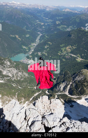 Mature man BASE jumping from mountain, Alleghe, Dolomites, Italy - Stock Photo