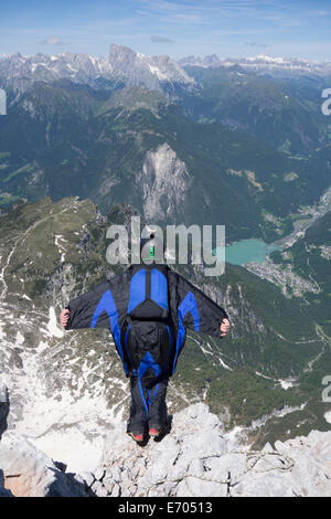 Mid adult man BASE jumping from mountain edge, Alleghe, Dolomites, Italy - Stock Photo