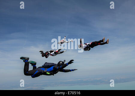 Four young adult male skydivers free falling, Siofok, Somogy, Hungary - Stock Photo