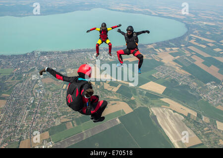 Three skydivers freeflying in formation, Siofok, Somogy, Hungary - Stock Photo