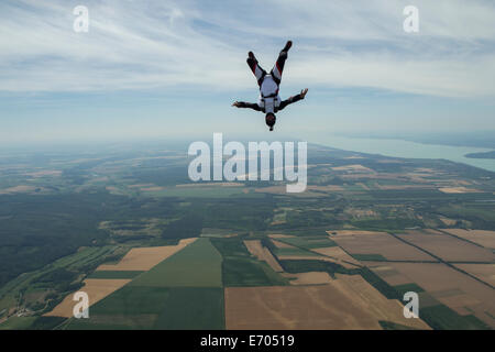 Male skydiver freeflying upside down above Siofok, Somogy, Hungary - Stock Photo